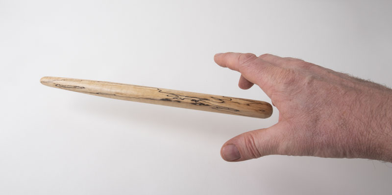 Hand reaching for a spirtle, or spurtle, in spalted birch